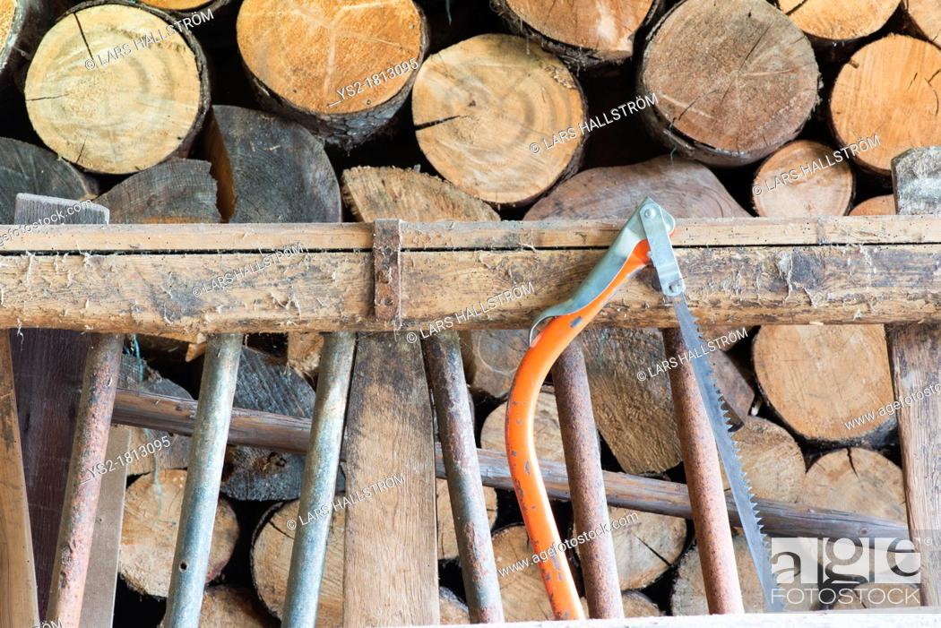 Imagen: Stacked timber and an old saw.
