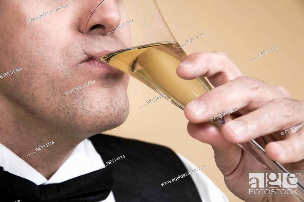 Stock Photo: Close-up of a man drinking from a glass of champagne.