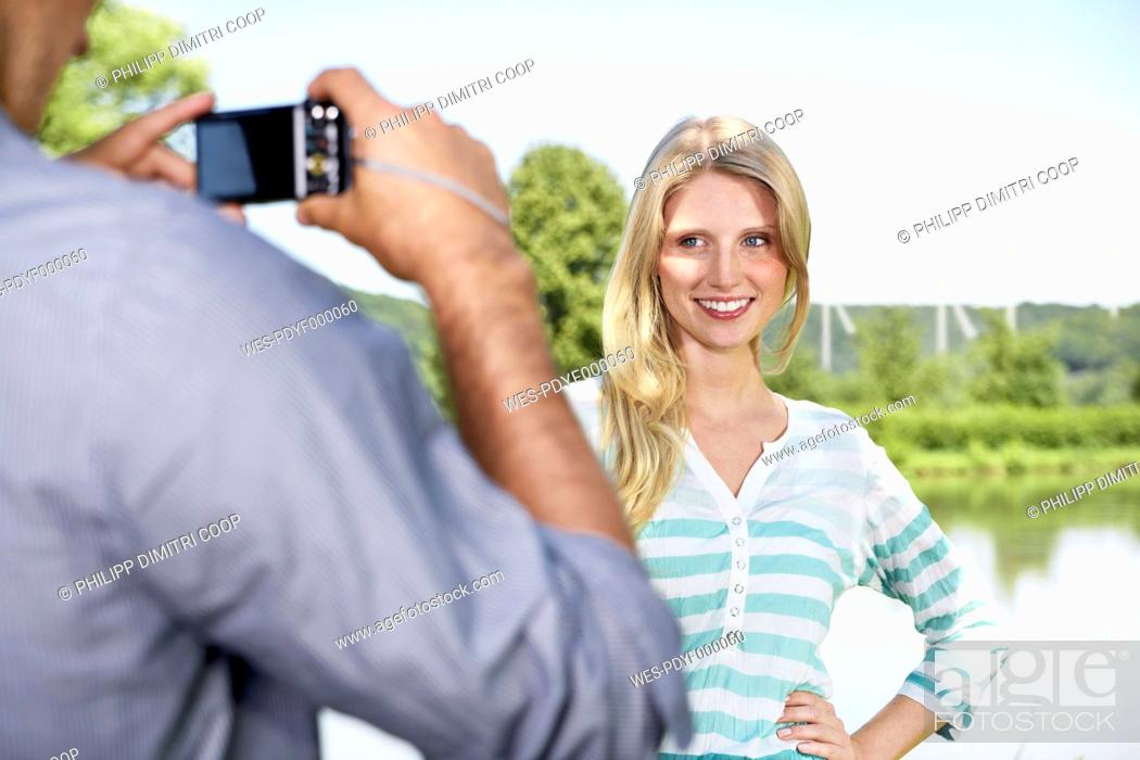 Stock Photo: Germany, Cologne, Young man taking photo of woman.