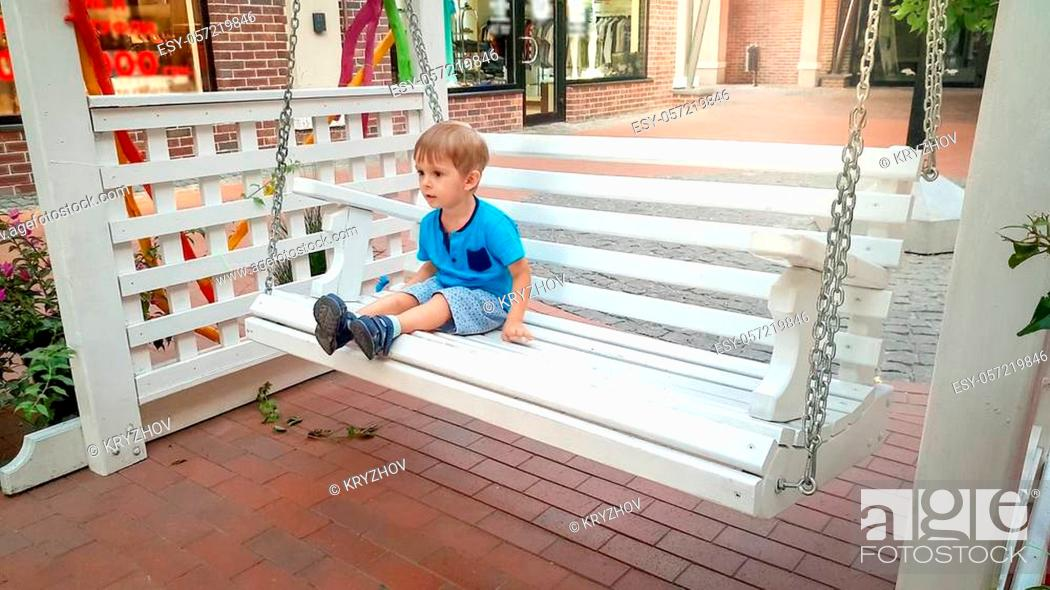 Stock Photo: Image of little toddler boy sitting on white wooden swing bench on old european town street.