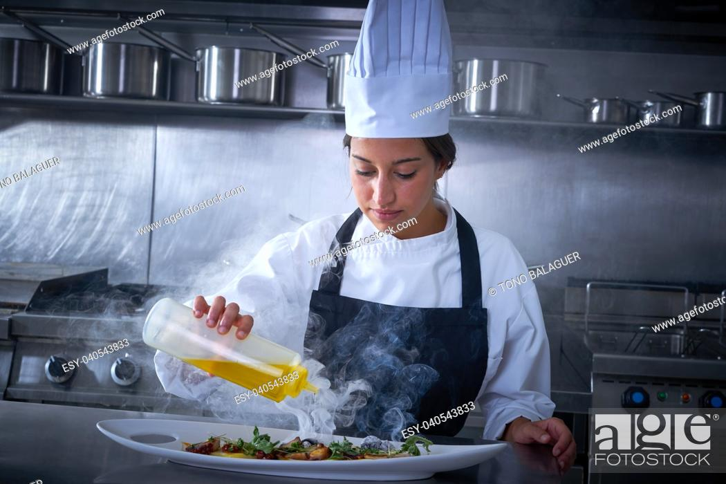 Stock Photo: Chef woman working in kitchen with smoke and oil.