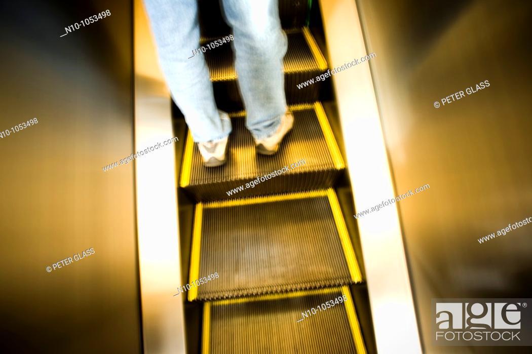 Stock Photo: Young man on an escalator.
