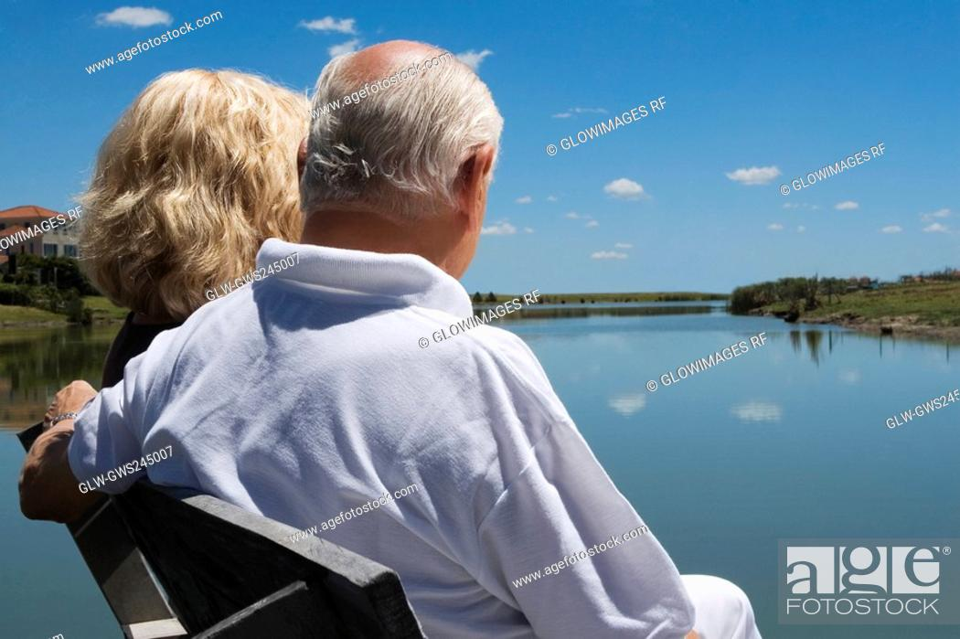 Stock Photo: Senior couple sitting on a bench at the lakeside.