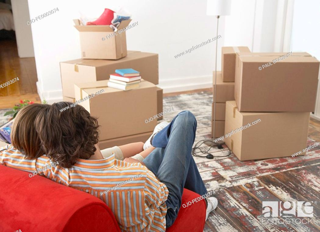 Stock Photo: Rear view of couple on red chair in house with cardboard boxes.