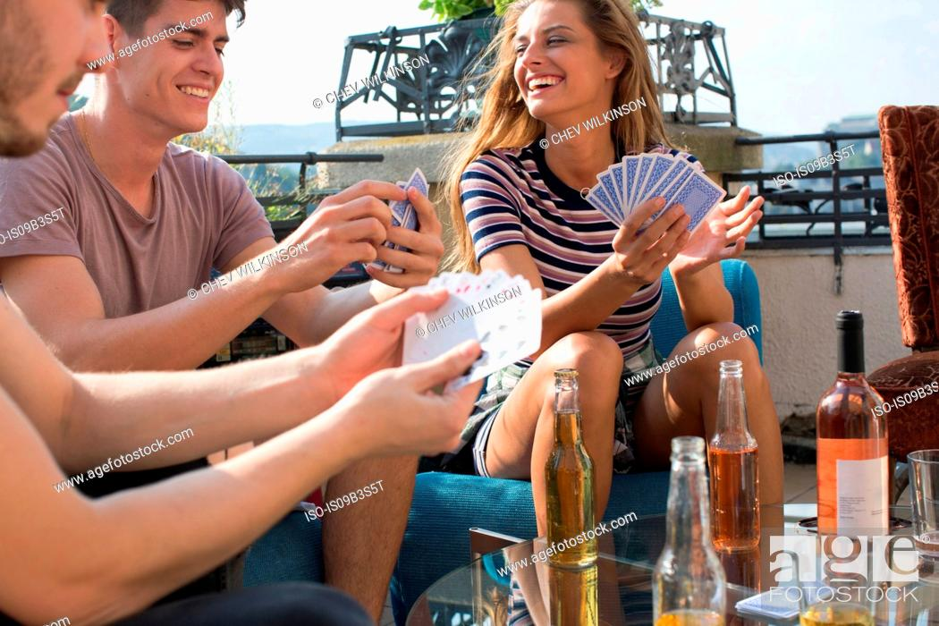 Stock Photo: Adult friends playing card games at roof terrace party.