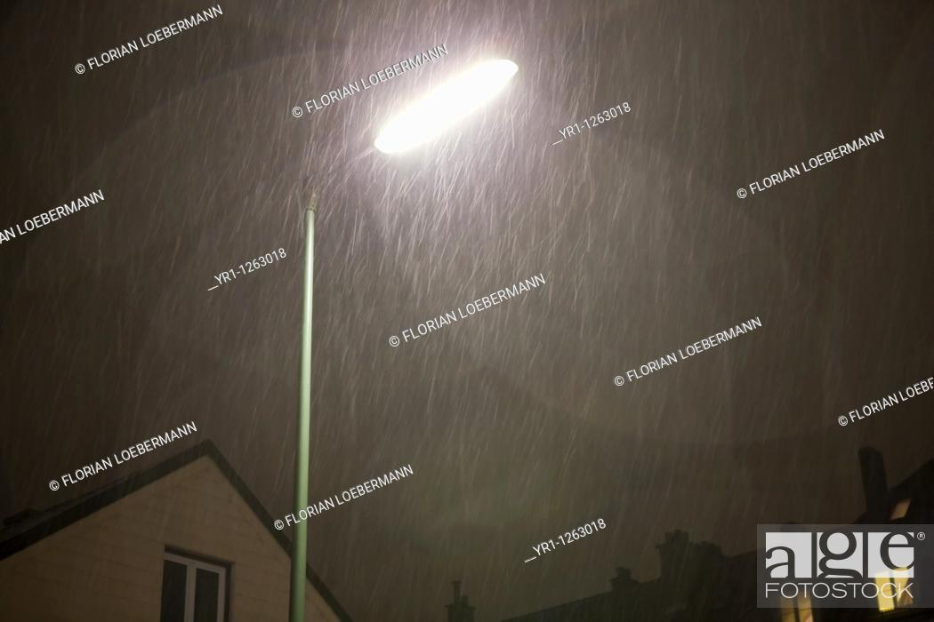 Stock Photo: Street light during snowfall at night. Residental houses in the backgroun, Munich, Germany.