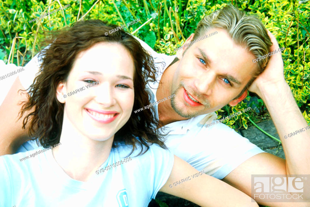 Stock Photo: Portrait of young couple lying in a garden.