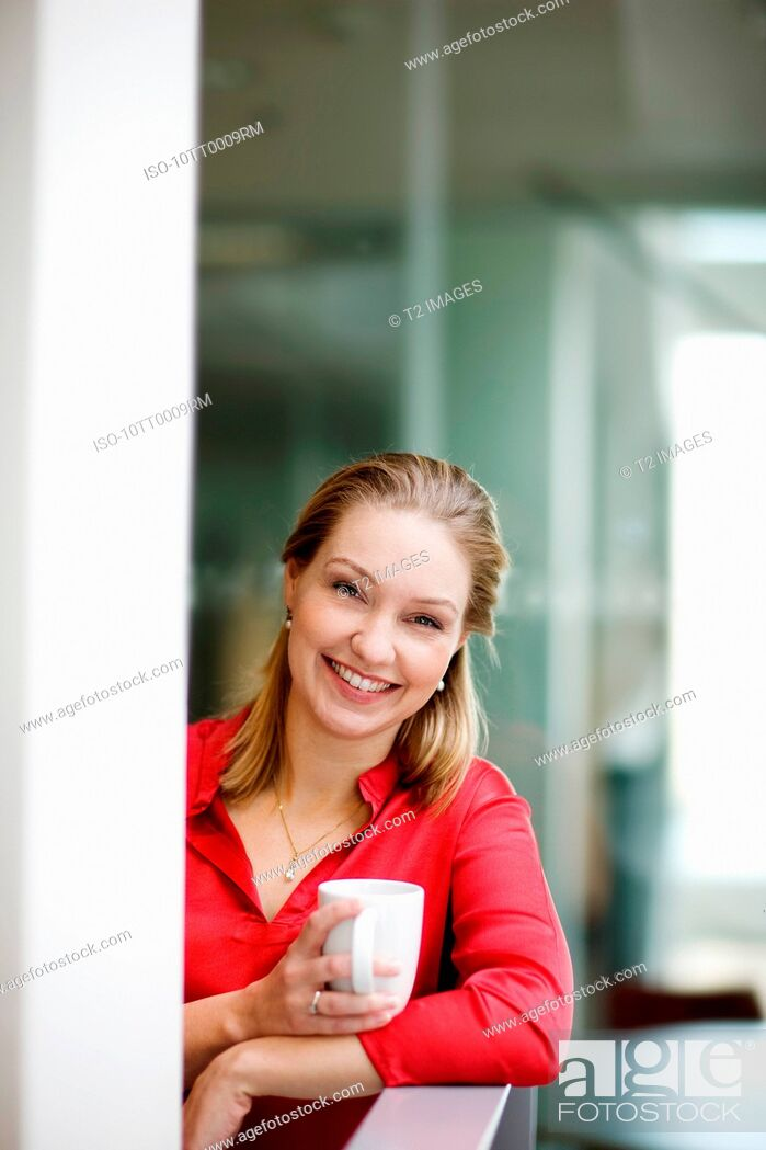 Stock Photo: Woman holding a cup, smiling.
