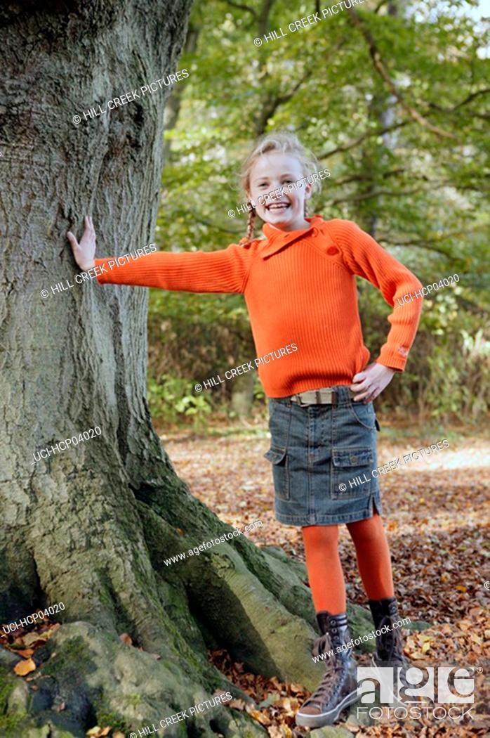 Stock Photo: Young girl leaning against tree.