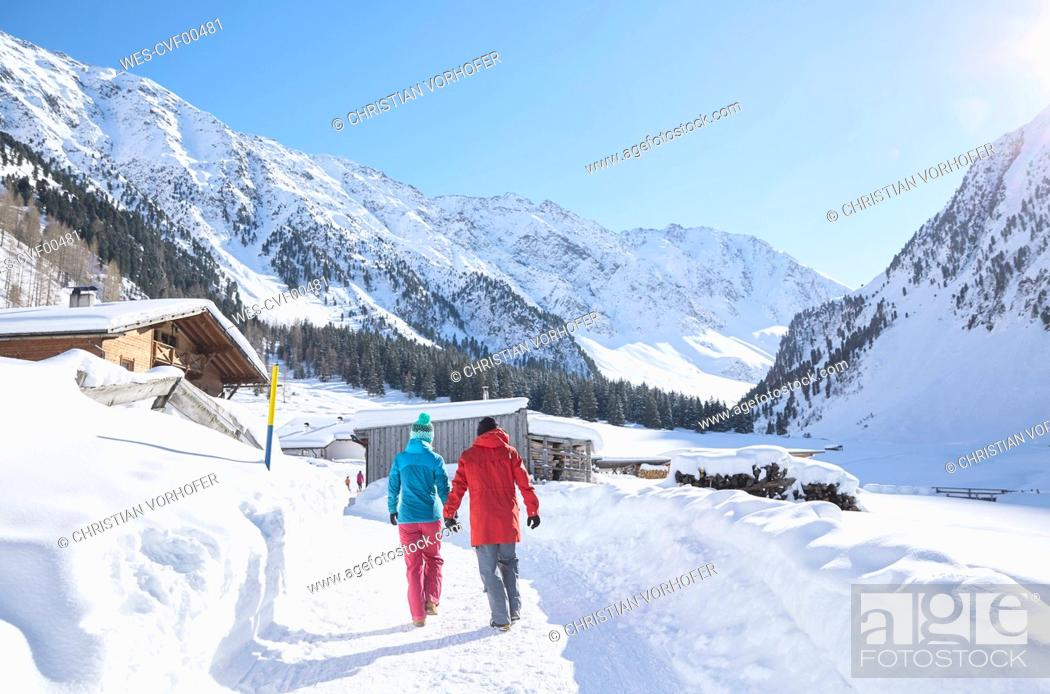 Stock Photo: Couple walking in snow-covered landscape.