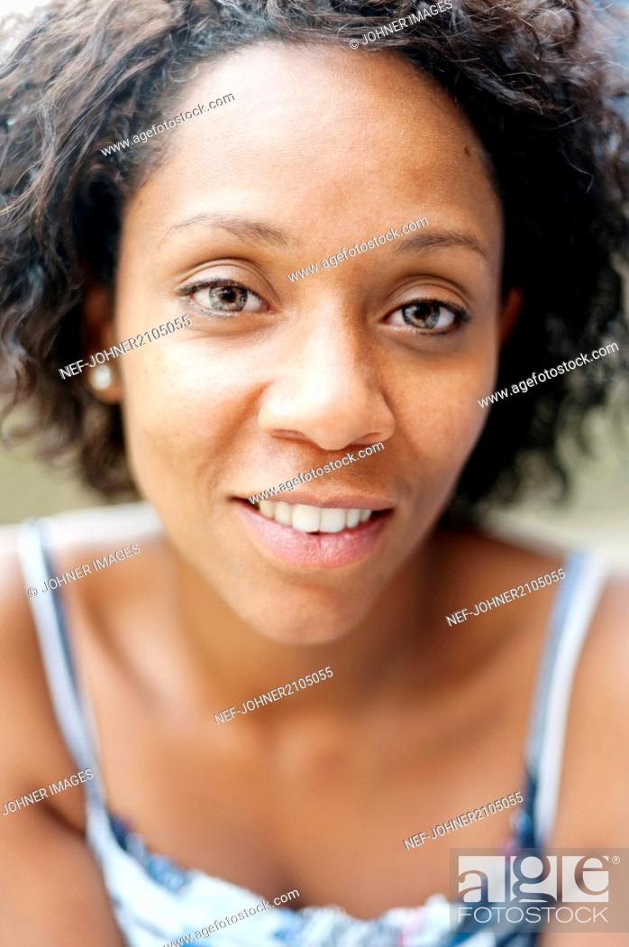 Stock Photo: Portrait of smiling woman with curly hair.