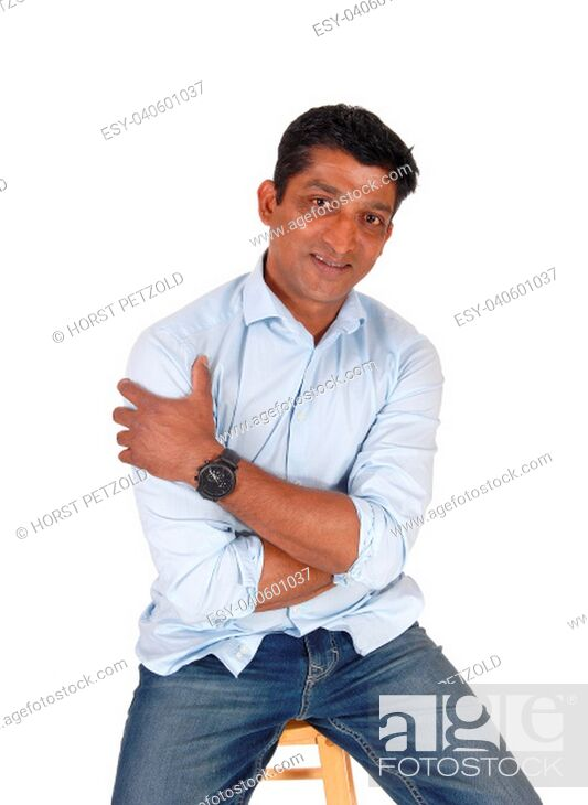 Stock Photo: A handsome middle age East Indian man sitting on a bar chair in.jeans and a blue shirt, isolated for white background.