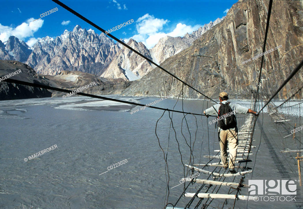 Stock Photo: Man crossing suspension bridge, Karakorum, Pakistan.