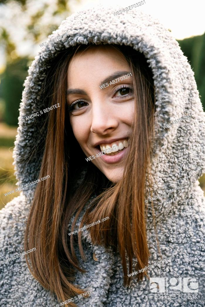 Photo de stock: Close-up of cheerful mid adult woman wearing hood in park during winter.