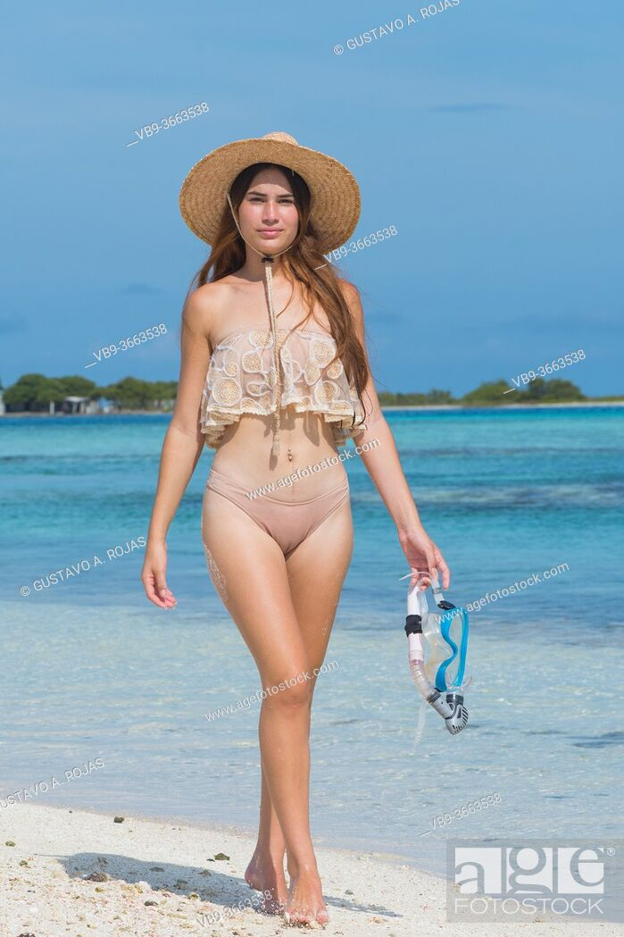 Photo de stock: Young woman with wet skin and snorkel standing on tropical sand beach going to swim at blue water sea.