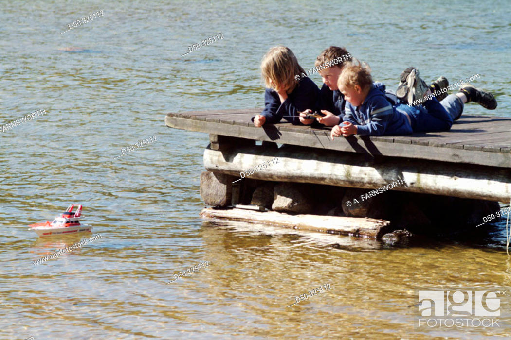 Stock Photo: Three boys, two aged 8, one aged 4, play with a radio controlled boat from a dock in Lake Vaettern. Medevi, Sweden.