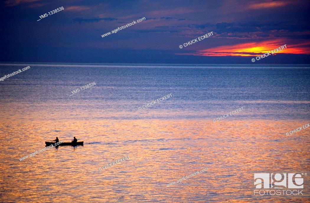 Stock Photo: Two men canoeing on Lake Superior at sunset.