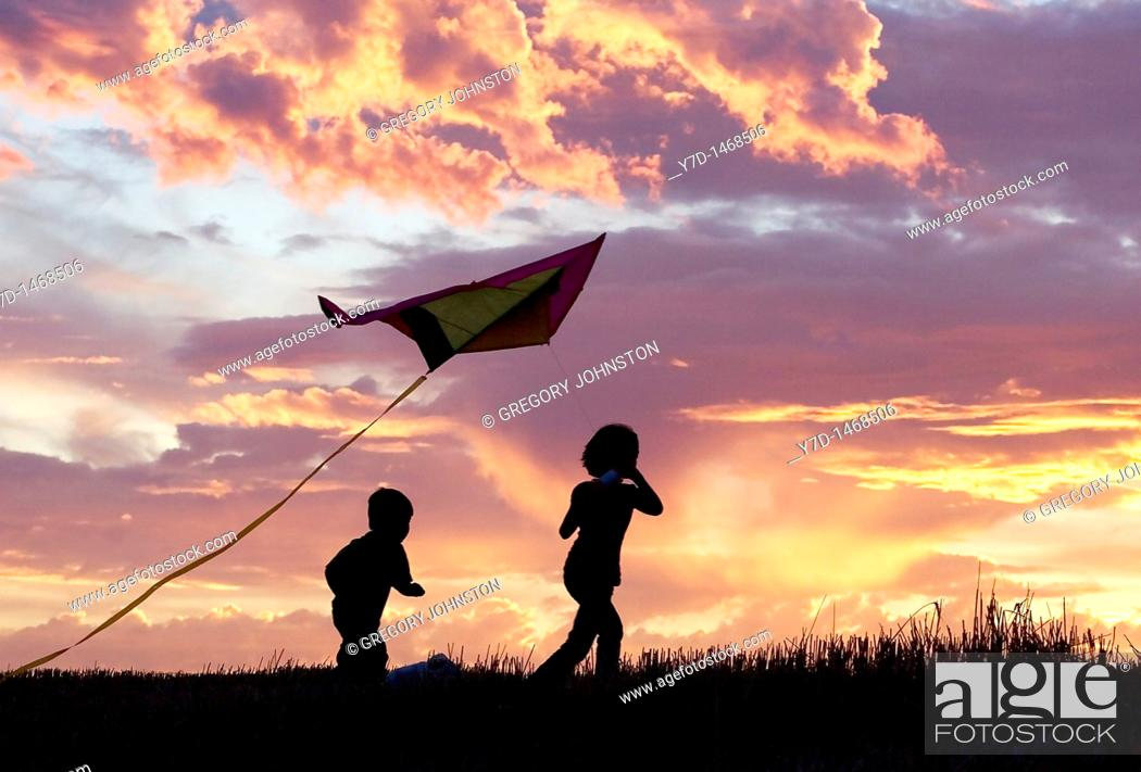 Stock Photo: A brother and sister getting a kite to fly suring sunset.