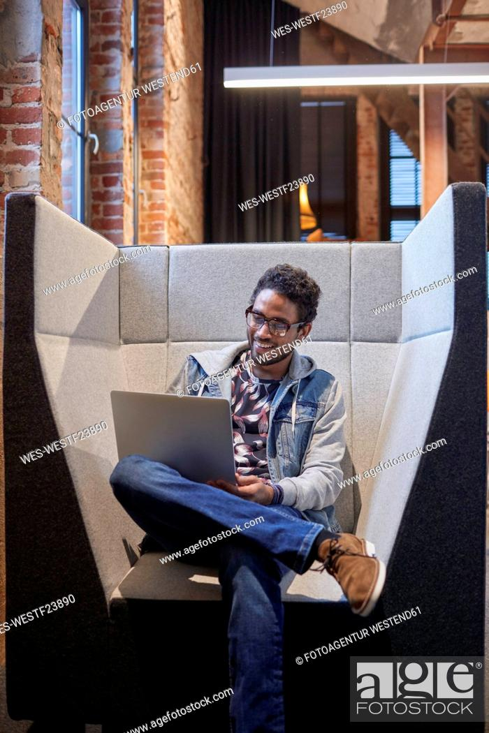 Stock Photo: Young man working in creative start-up company, using laptop.