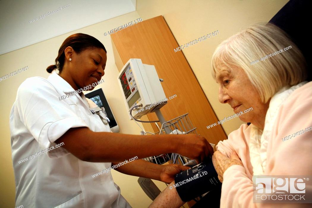 Stock Photo: A nurse attaches an inflatable cuff to the arm of an elderly woman. The cuff is part of a sphygmomanometer blood pressure monitor.