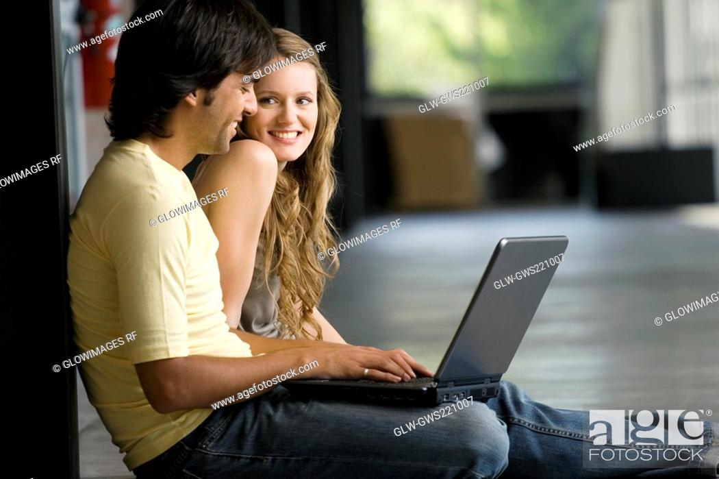 Stock Photo: Young woman sitting with a young man working on a laptop.