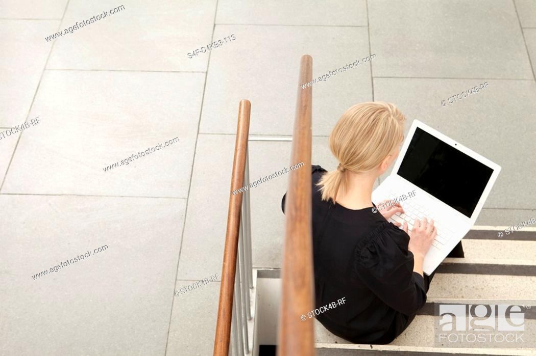 Stock Photo: Woman using laptop on stairs, Munich, Bavaria, Germany.