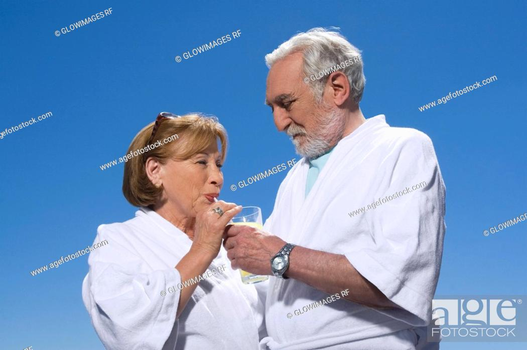 Stock Photo: Low angle view of a senior woman drinking juice from a glass held by a senior man.