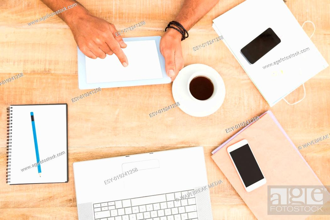 Stock Photo: Hands using tablet next to several devices.