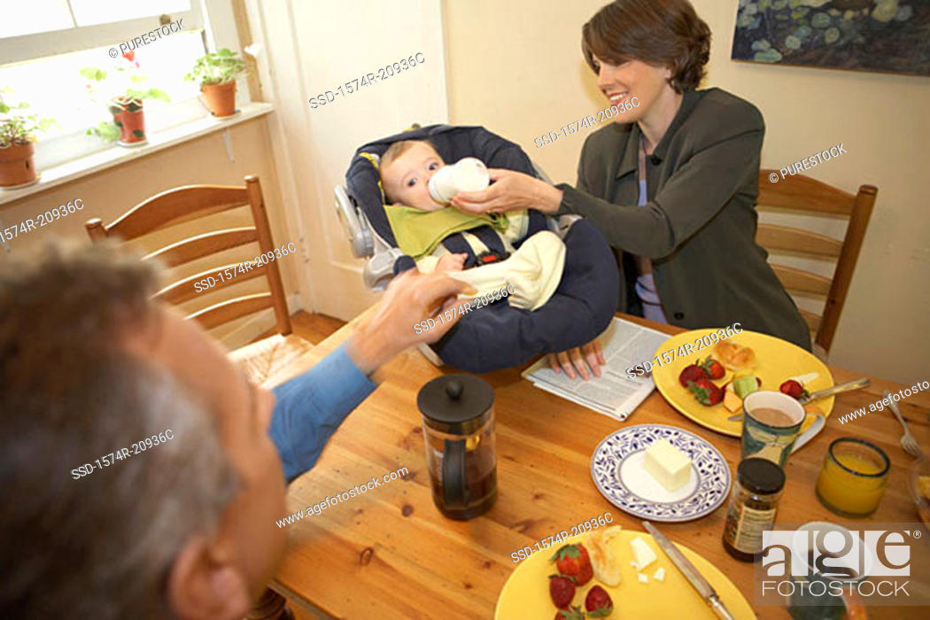 Stock Photo: High angle view of a mid adult couple with their son at a dining table.