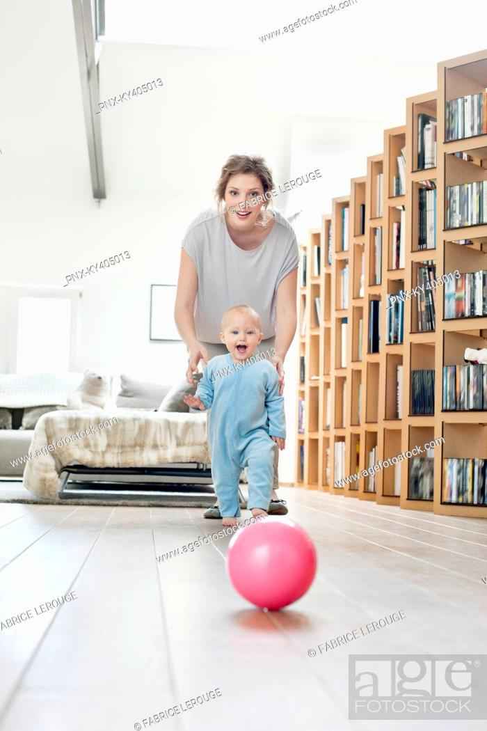 Stock Photo: Woman playing with her daughter walking towards a ball.