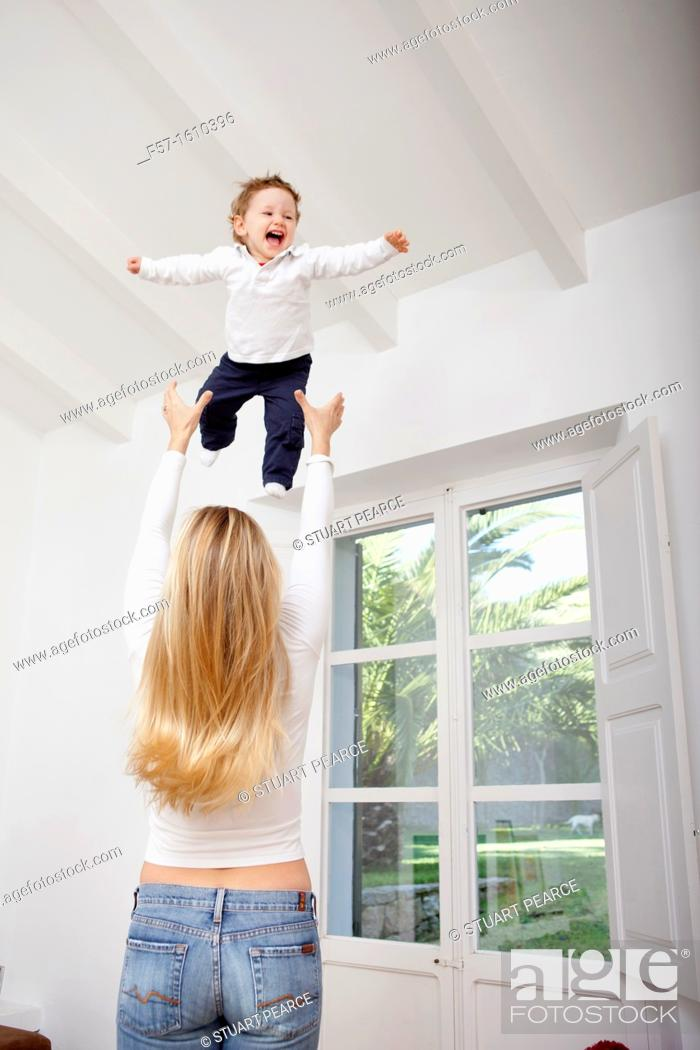 Stock Photo: Mother throwing her one year old boy in the air.