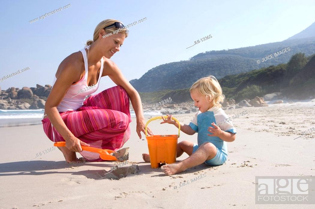 Stock Photo: Mother and daughter 1-3 with bucket and spade on beach.