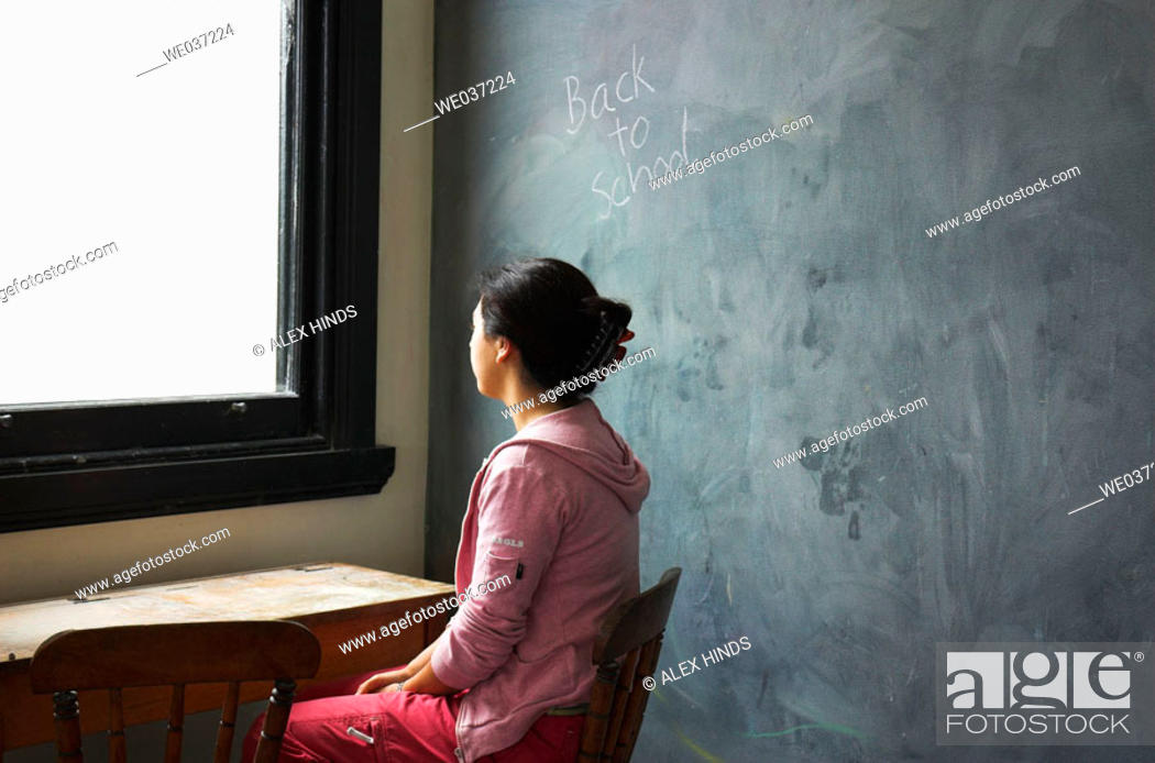 Stock Photo: Young woman sitting at old school desk with blackboard behind her and the words 'back to school' on board.