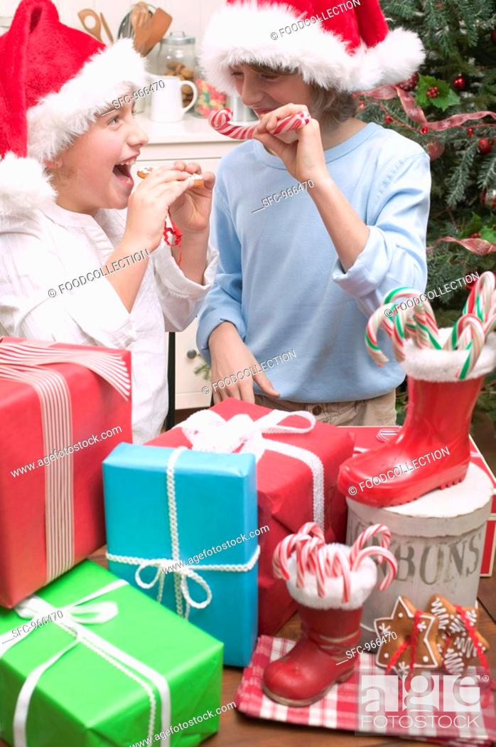 Stock Photo: Girl and boy in Father Christmas hats with gifts.