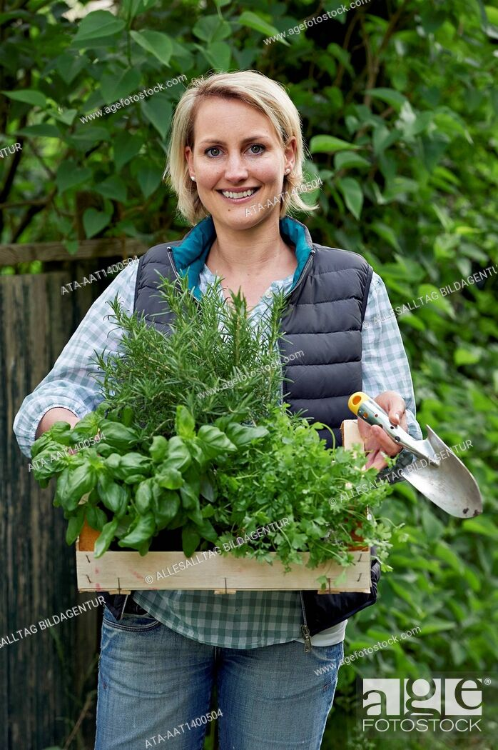 Stock Photo: Woman in the garden with a basket full of herbs.