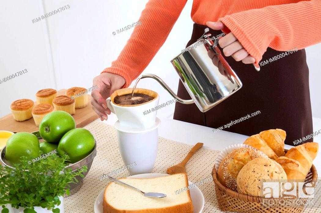 Stock Photo: Young woman making coffee in the kitchen for breakfast,.