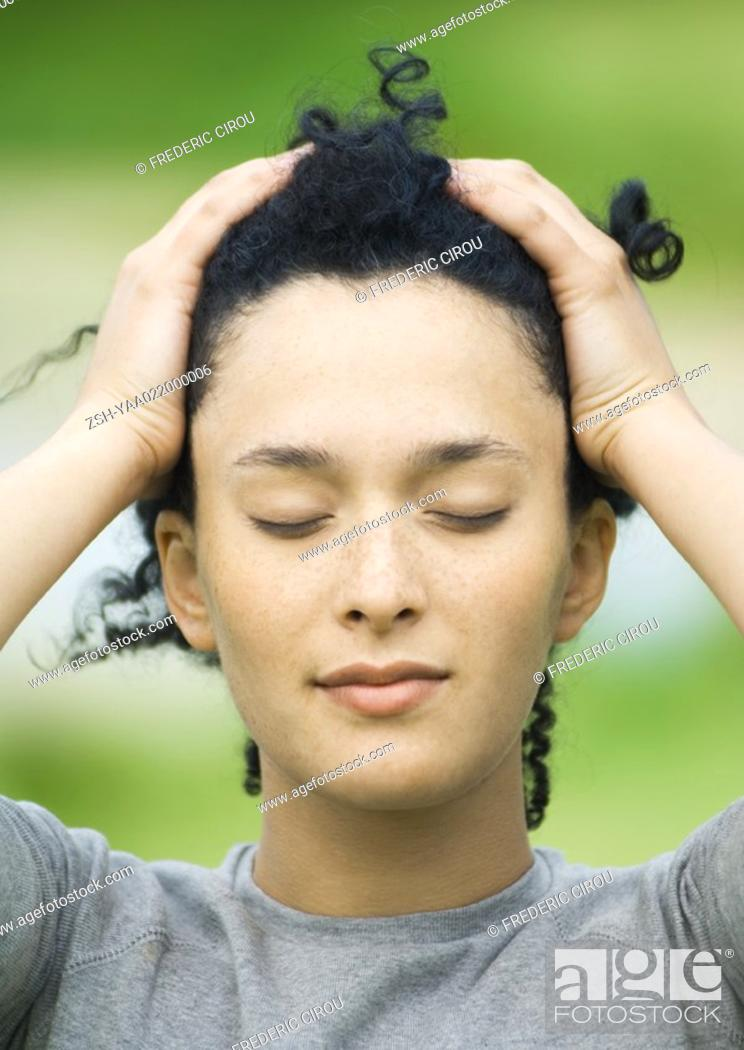 Stock Photo: Young woman pushing hair back, eyes closed, portrait.