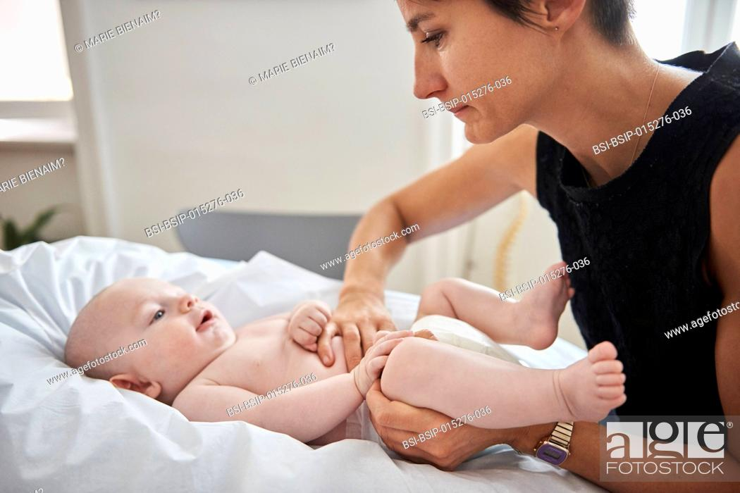 Stock Photo: Reportage on a physiotherapy and osteopathy practice in Lyon, France. Osteopathy session with a baby to help digestion and rebalance the skeleton.