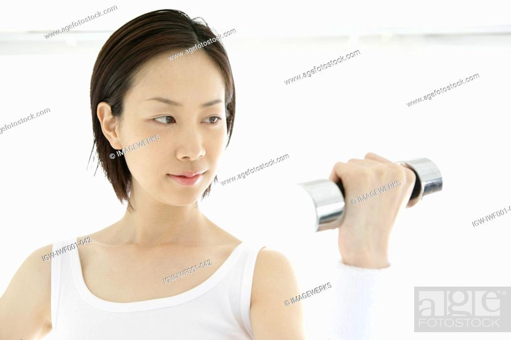 Stock Photo: Front view of a young woman lifting the dumbbell.