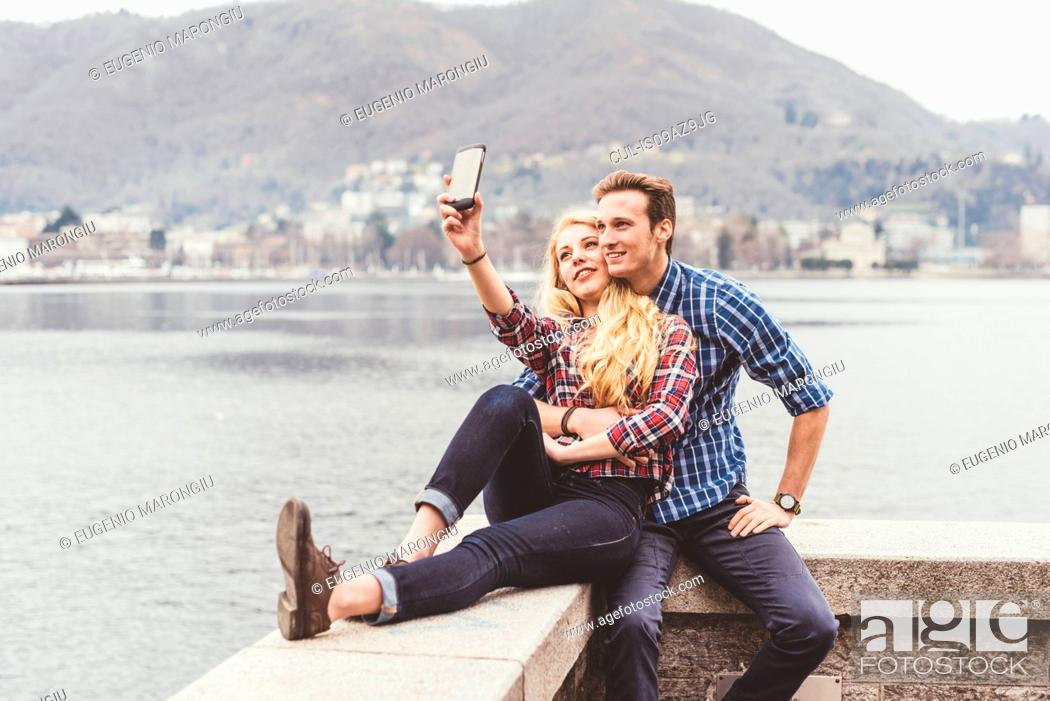 Stock Photo: Young couple sitting on harbour wall taking smartphone selfie, Lake Como, Italy.