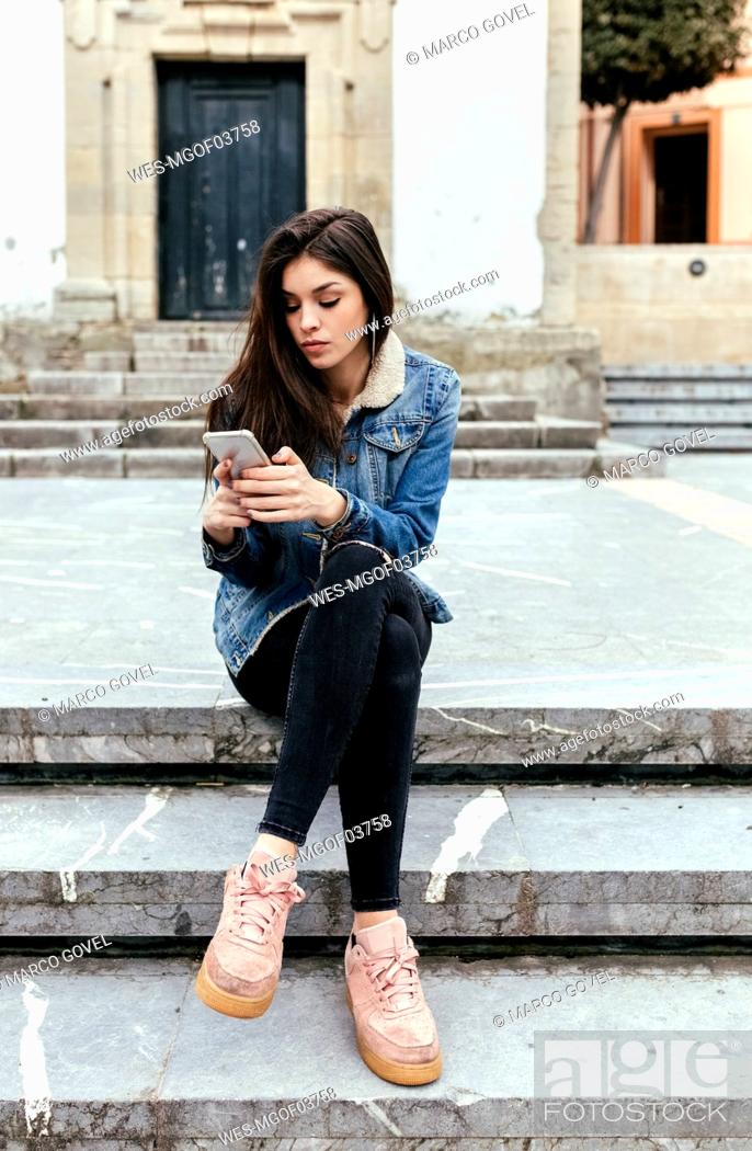 Stock Photo: Young woman sitting on stairs in a town checking her smartphone.