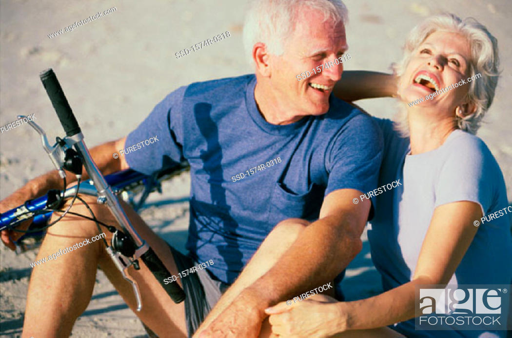 Stock Photo: Senior couple standing with bicycles laughing.