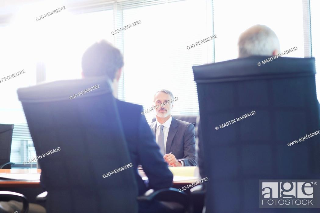 Stock Photo: Businessmen meeting in sunny conference room.