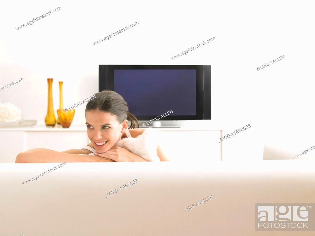 Stock Photo: Woman sitting on sofa in modern living room.