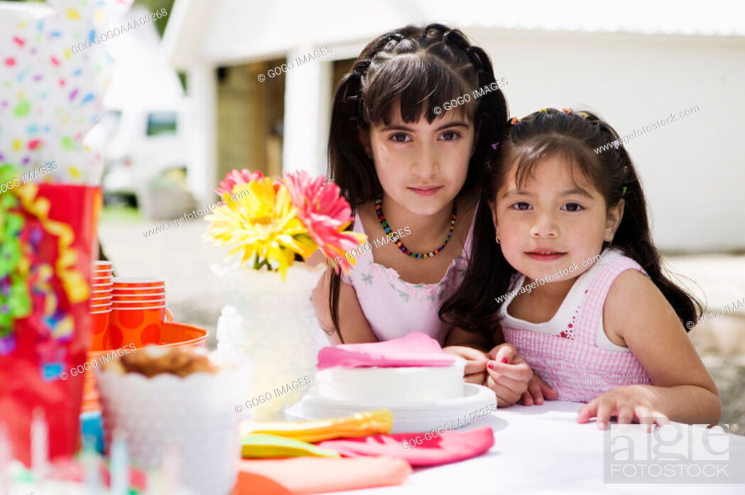 Stock Photo: Two girls 4-7 by table, portrait.