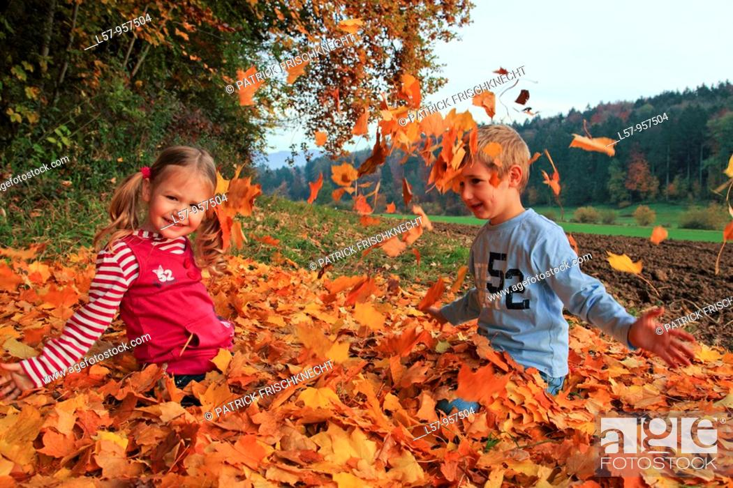Stock Photo: girl and boy playing in pile of leaves, fall Zuerich, Switzerland.