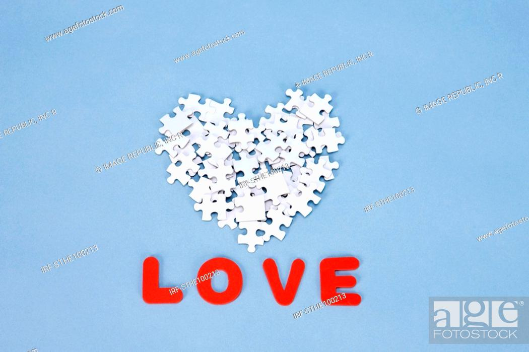 Stock Photo: heart shape made by pieces of puzzle and LOVE.