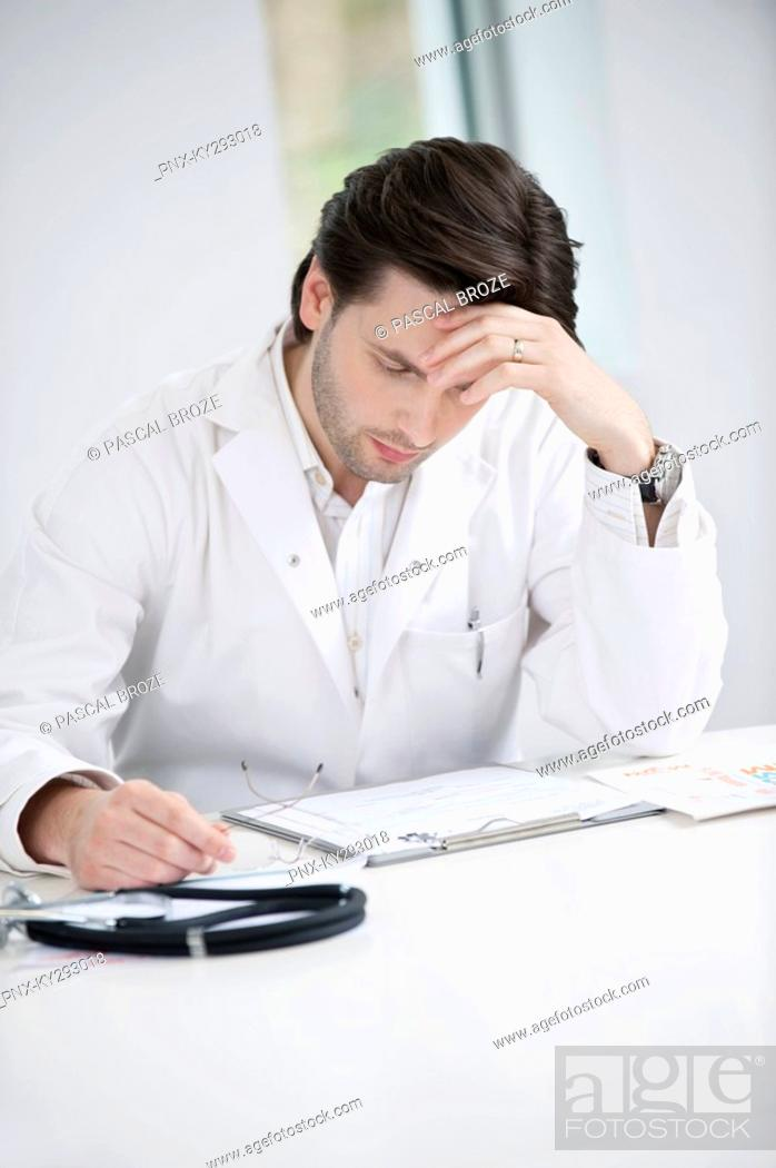 Stock Photo: Male doctor examining a medical report and looking upset.