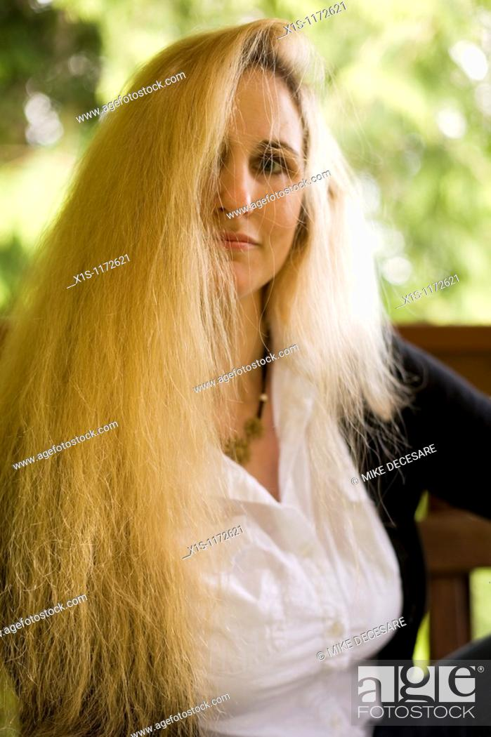 Stock Photo: 1/2 length shot of an attractive woman with very long, blond hair that covers part of her face, sitting outside.