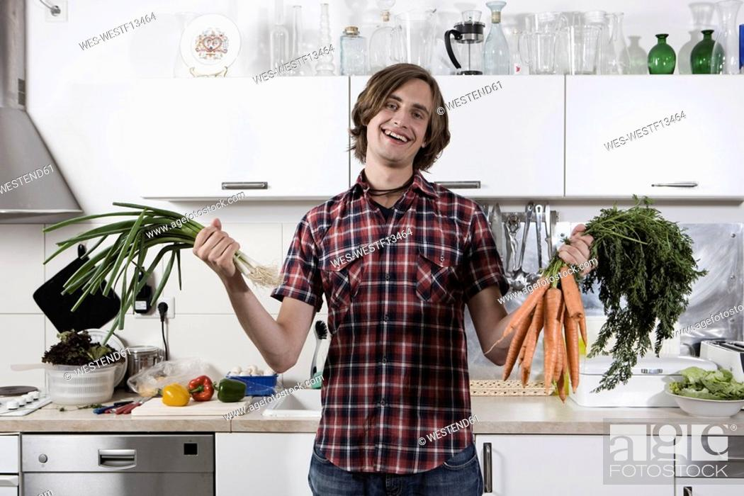 Stock Photo: Germany, Berlin, Young man in kitchen holding bunch of carrots and spring onions, laughing, portrait.
